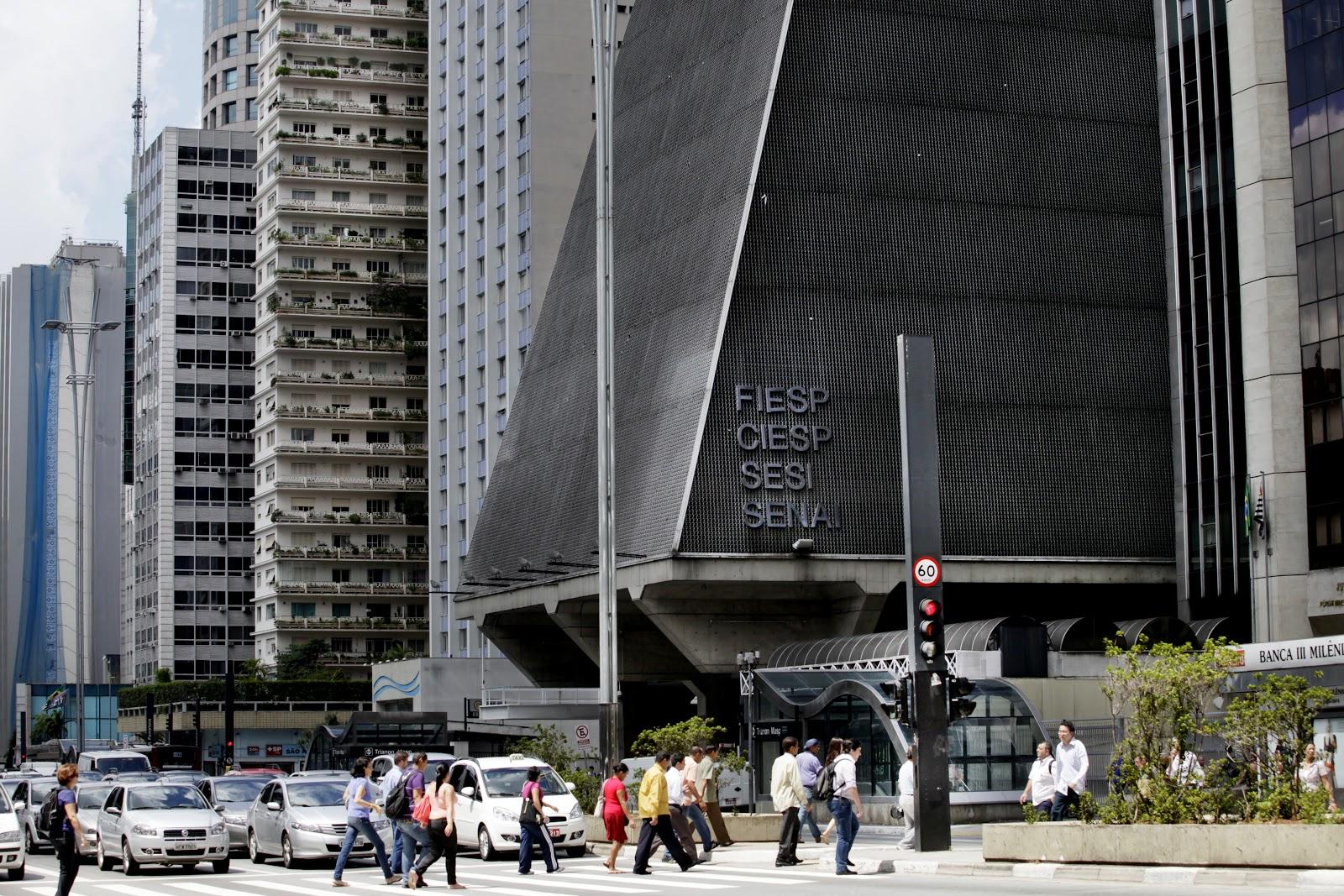 Pessoas atravessando a Avenida Paulista, da esquerda para a direita, no farol fechado para carros e, ao fundo, o Centro Cultural Fiesp.