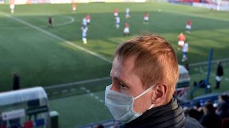 Un aficionado al fútbol, durante un partido al principio de la pandemia.