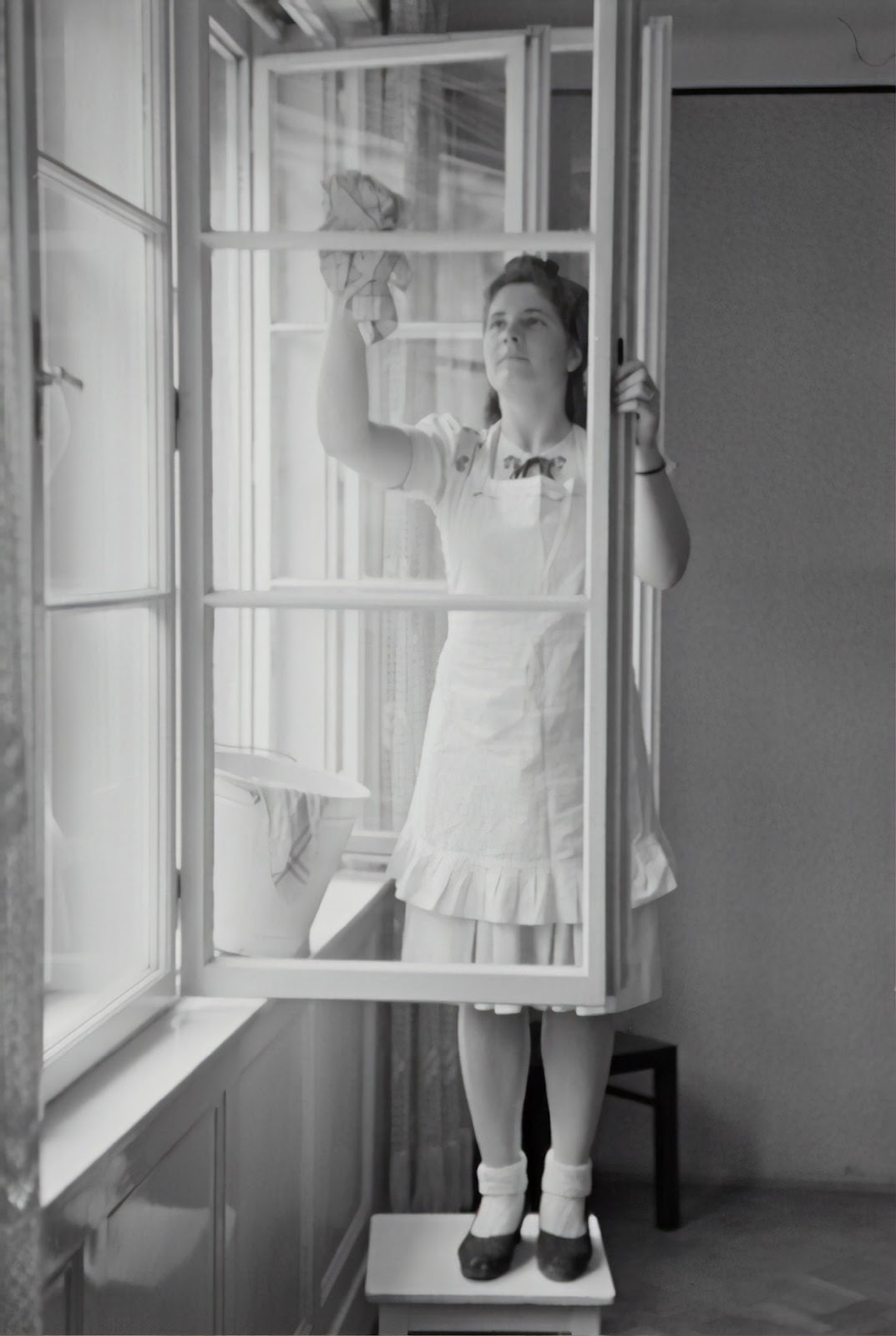 A person standing in front of a window  Description automatically generated