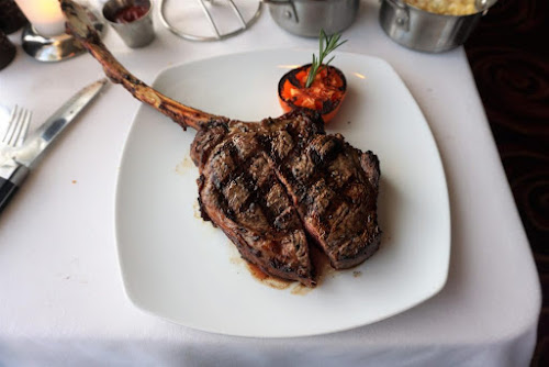 A bone-in Tomahawk rib eye steak entrée at Cagney's Steakhouse on Norwegian Sky.