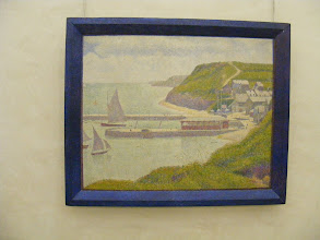 Photo: Seurat's Harbor at Port-en-Bessin at High Tide. From the Orsay's Web site: The overall composition, both geometrical and asymmetrical, plays alternately on the slanting lines of the cliffs and the flat lines of the jetties and the horizon, punctuated in turn by the upright masts. The road winding up from Port-en-Bessin to the edge of the cliffs softens the strict construction, a frequent device in Seurat's work. The wild grasses in the foreground introduce an untidy note in this motionless landscape. The port emptied of all human presence leaves an abandoned, melancholic impression.
