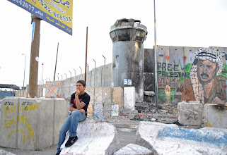 Photo: A young boy sits outside Qalandiya checkpoint prior to the spark of clashes.