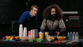 Reggie Watts Wears a Purple and Yellow Quilted Sweatshirt
