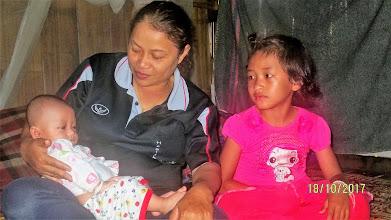 Photo: Jia Jan village: baby with older sister and Kanda (volunteer healthcare worker)