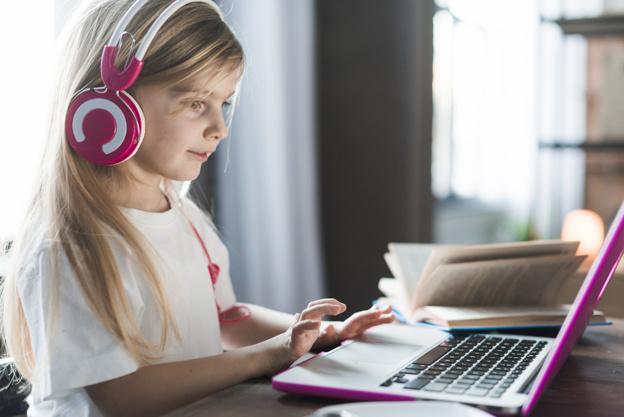 Girl using pink laptop Free Photo