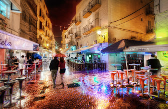 Photo: A Rainy and Romantic Night in Ibiza Old Town (Villa d'Eivissa)  Part of Ibiza is an old walled medieval town that is surrounded by layers of winding streets old shops intermixed with homes.  A few streets away from the walls, some of the streets are full of pubs and quirky shops...  I think it's better to explore them at night than in the day -- and especially so in the rain.  On this night, it was a little chilly and rainy, but that does not effect my camera.  I've never had a problem because of rain or cold or heat or <em>anything</em>.  It just works!  The rainy streets were full of colors and life.  I saw this couple quickly walking under an umbrella so I took a quick one to capture the scene.  from the blog at www.stuckincustoms.com