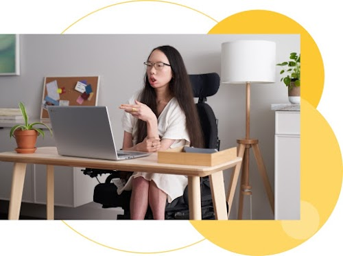 A person in a wheelchair sits at a desk with an open laptop.