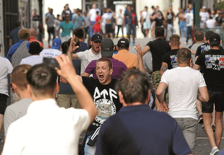 A brawl broke out between football fans in the French city of Marseille ahead of England's European Championship clash with Russia. Bare-chested English and Russian supporters hurled bistro chairs and bottles at each other. Picture: GALLO IMAGES/AFP/JEAN CHRISTOPHE MAGNENET