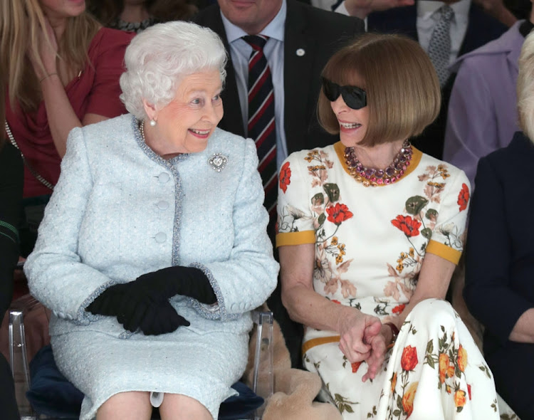 Queen Elizabeth II sits next to Anna Wintour as they view Richard Quinn's runway show at London Fashion Week.