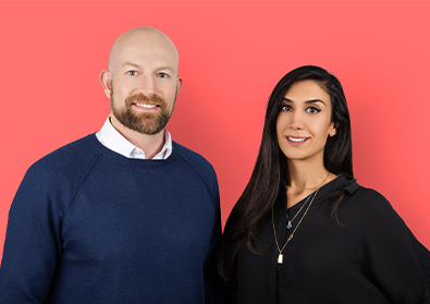 Cofounders Peter Fish and Shardi Nahavandi smile at a camera against a pink backdrop.