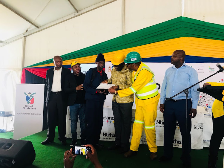 Ekurhuleni mayor Mzwandile Masina, along with Gauteng Premier, David and Makhura and the Provincial MEC for Human Settlements hand over a title deed to Abraham Molefe. Molefe is a one of 2000 to receive a serviced stand as part of the provincial government's Rapid Land Release Programme.