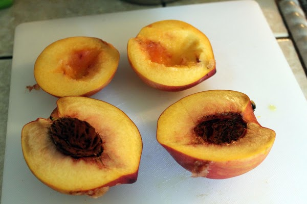 Cutting peaches in half.