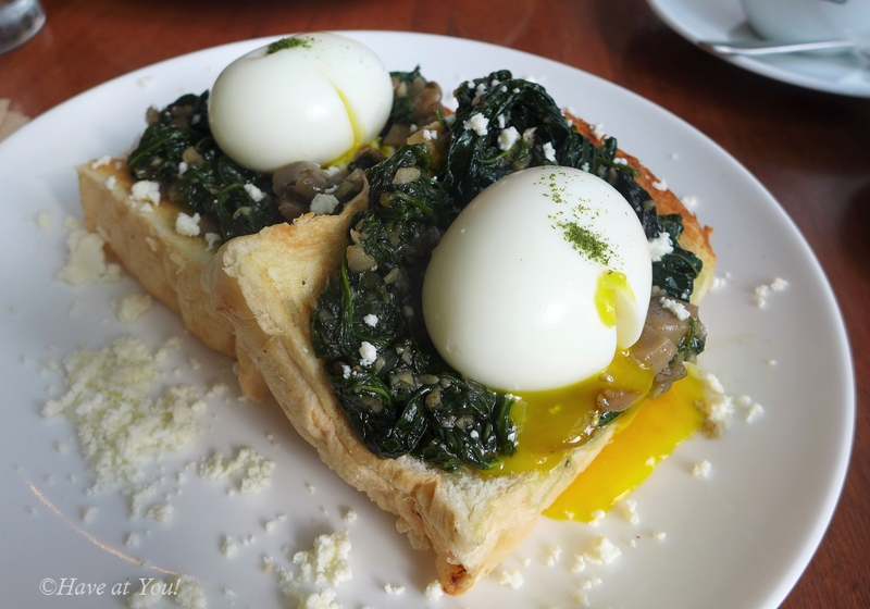 two slices of toast topped with spinach, mushrooms and soft boiled eggs
