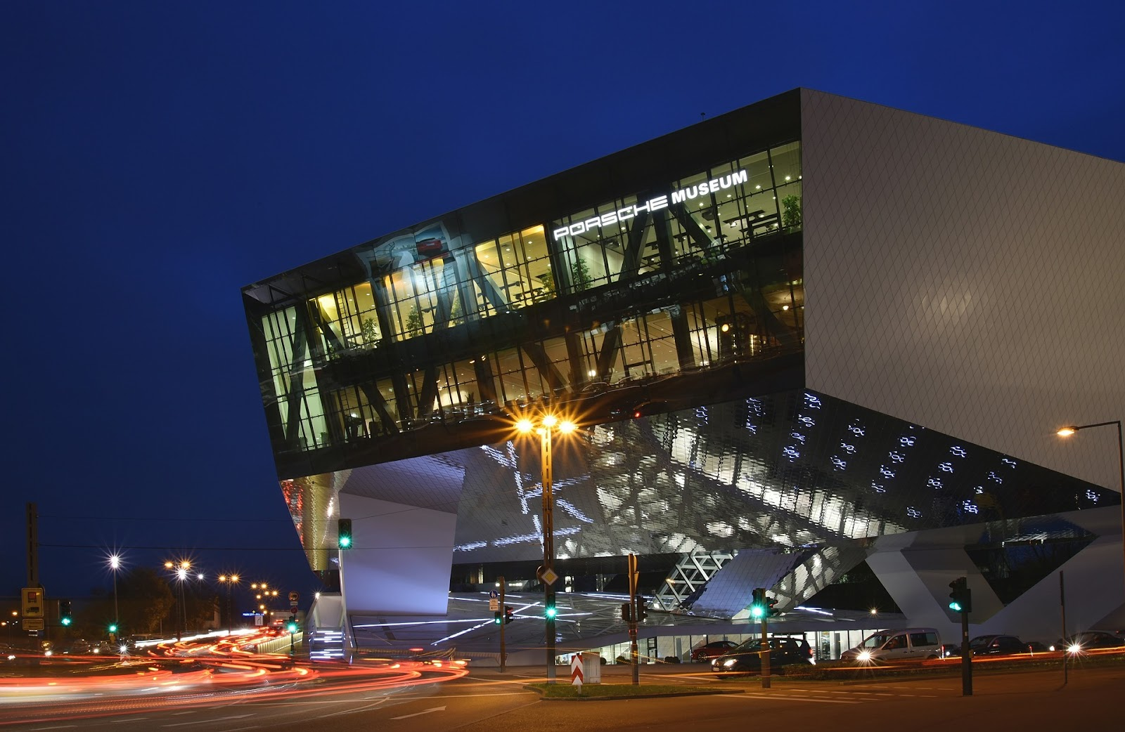 porsche museum main building modern architecture seen from nearby street at night time