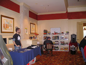 Photo: Nat at the Geek Out Cafe table, with the game library in the far side.  You can see Ernie looking for an expiration date on a board game, I think.