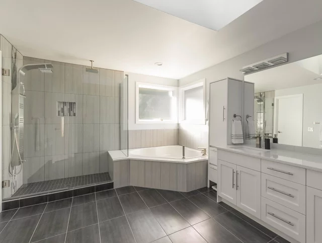 contemporary bathroom design with corner soaking tub, white shaker cabinets, chrome hardware, grey tile floors and glass shower door