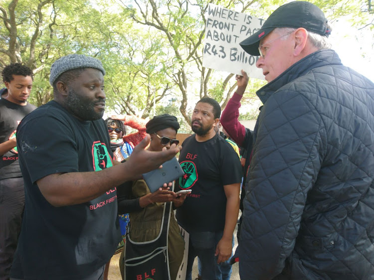Peter Bruce confronts the protesters outside his home.