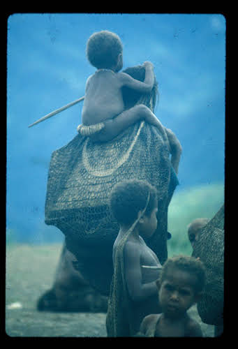 Papua. Tribes Baliem Valley Time Travel. Mother carrying her child the traditional way