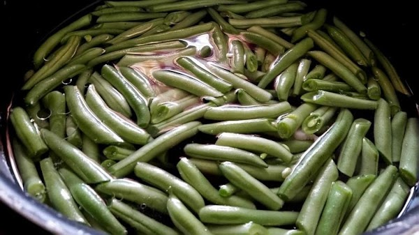 Steam or boil green beans until almost tender. They will cook longer in the...