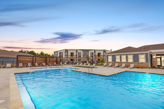 Swimming pool with lounge chairs and cabanas, next to clubhouse and apartment buildings at dusk
