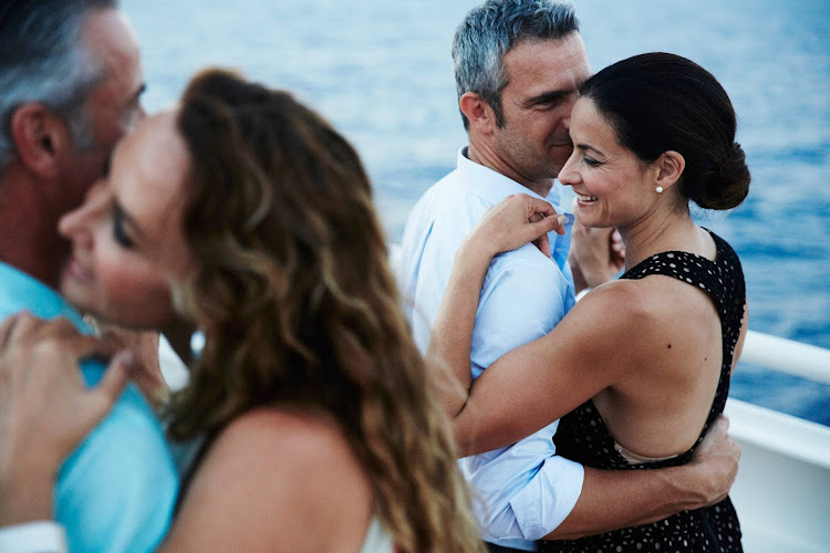 Couples dance to live entertainment at twilight during a Seabourn cruise.