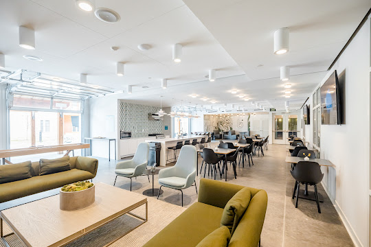 Resident lounge with a seating area, several tables with chairs, mounted TVs, bar and barstools, and full kitchen