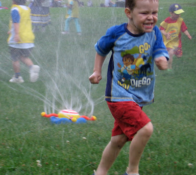 BigE running through the water sprinkler