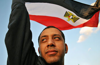 Photo: A man raising the Egyptian flag during the demonstration.