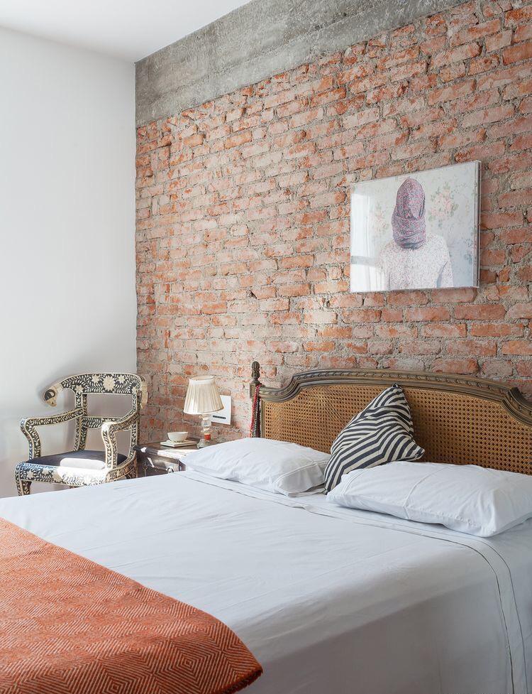 O quarto exibiu a beleza original da estrutura da parede com viga de concreto e tijolo aparente. Elementos como a cadeira, a cabeceira e o abajur com cara de retro, deram o toque moderno do projeto.