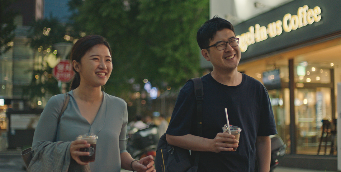Founders, Suji and Han, are walking with drinks in their hands along a dimly lit sidewalk.