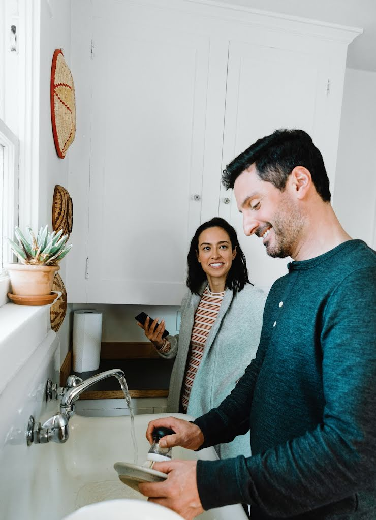 A smiling man scrubs dishes in a kitchen sink while a smiling woman, a phone in her hand, watches.