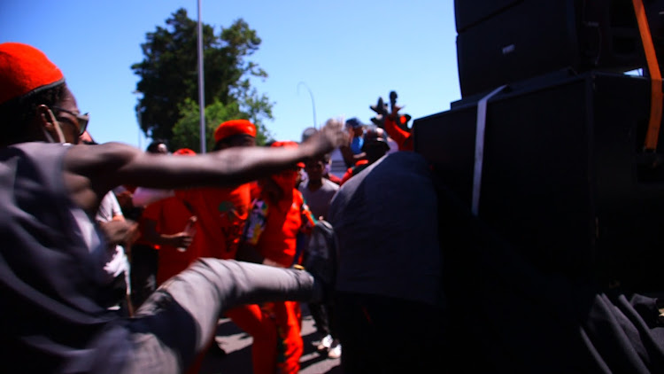 An EFF protester aims a kick at the Lycra-clad mad who tried to interrupt party secretary-general Marshall Dlamini outside Brackenfell High School in Cape Town on November 20 2020.