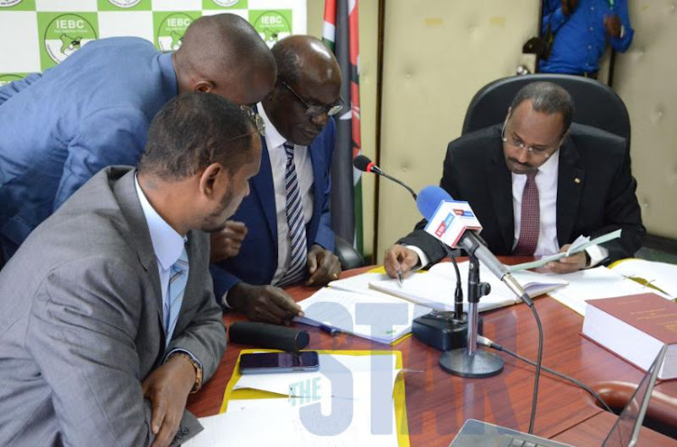 IEBC chairperson Wafula Chebukati with commissioner Abdi Guliye verify the BVR machine with Mariga's name at the IEBC headquarters on September 13, 2019.