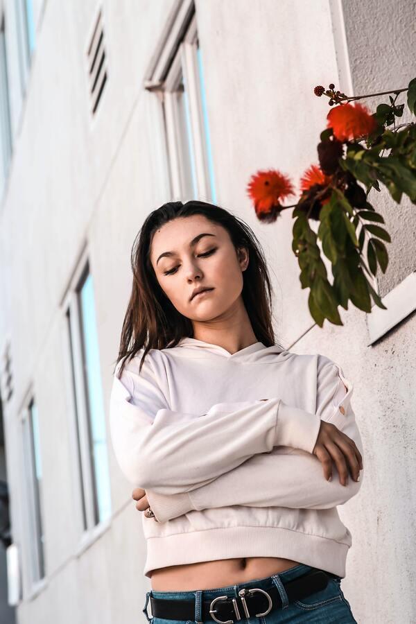 Mulher branca com os braços cruzados posando ao lado de uma flor