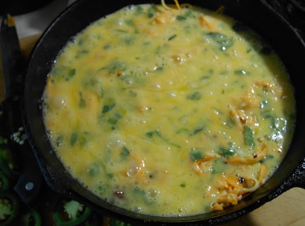 Break eggs into a bowl, add cilantro and whisk.  Pour over cheese.