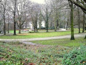 Photo: Ein Blick von unterhalb des Parkplatzes auf den Stadtgarteneingang an der Grünstraße. Im Hintergrund die Urologie bzw. Kinderhlinik des Allgemeinen Krankenhauses. Links außerhalb des Bildes befindet sich der Spielplatz mit seinem schaukelnden Pferd für junge Rodeoreiter.