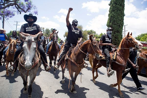 Randy and The Compton Cowboys leading a group of thousands on horseback through the streets of Compton wearing Compton Cowboy merch, cowboy hats, and fists raised.