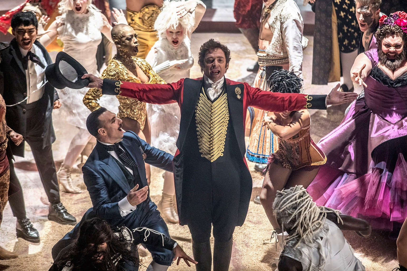 image from the movie The Greatest Showman, the main character with his arms open wide at the end of the show with characters around him.