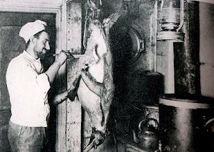 Photo: El cocinero Charles Green despellejando un pingüino en la cocina .