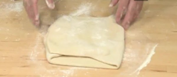 Fold in the butter:Unwrap chilled butter and place onto dough. Fold dough around butter...