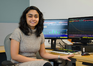 Photo: Husain with the Bloomberg terminal, the most widely used information system in the finance industry. The terminal was purchased recently by the School of Business.