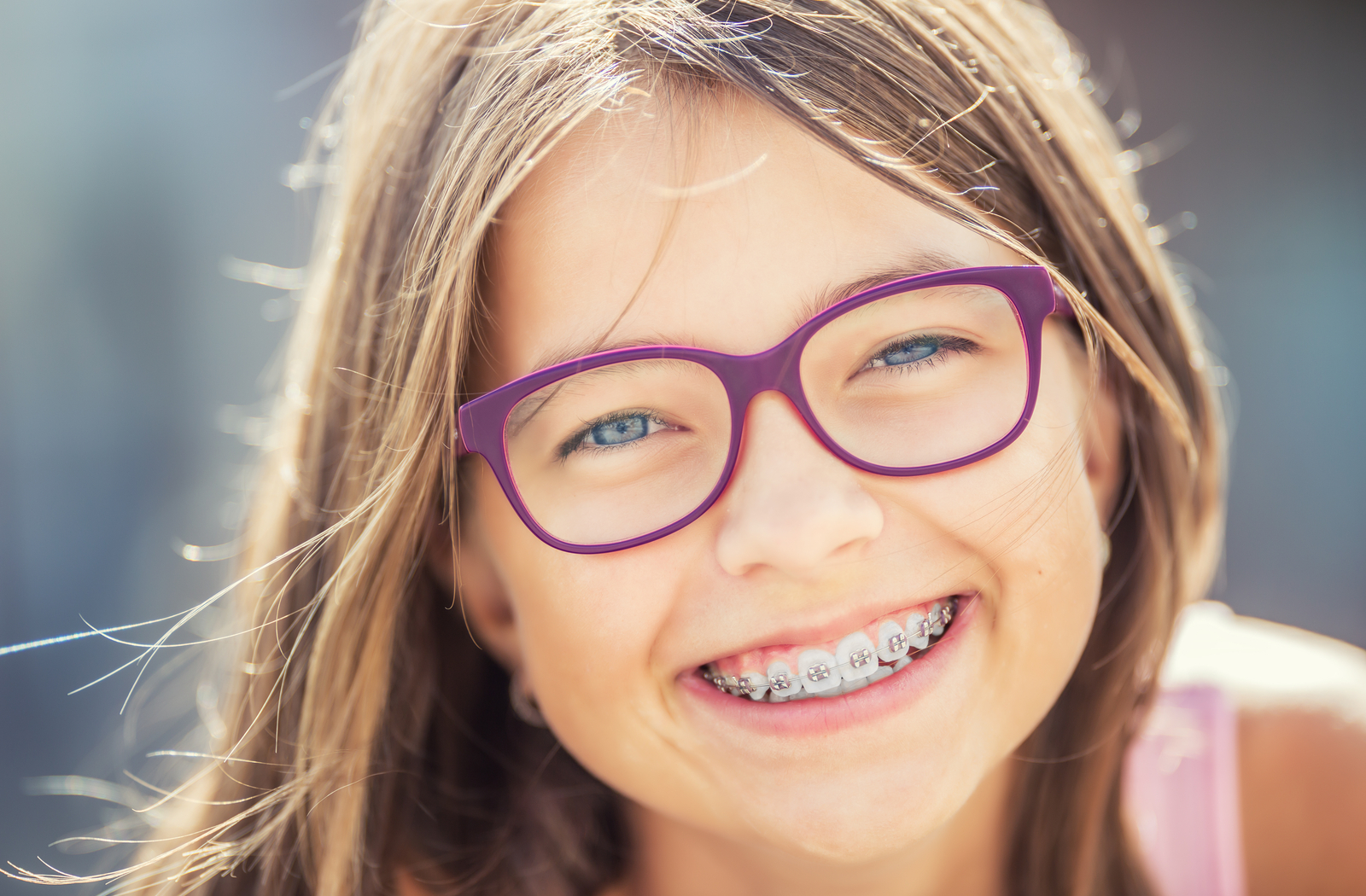 blonde child smiling with braces wearing purple glasses