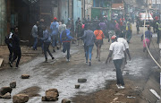 Residents and traders run during clashes between traders and riot police, following demolitions of their homes and stalls amid the spread of Covid-19, near the Korogocho market, within Kariobangi settlement of Nairobi, Kenya, on May 8 2020.