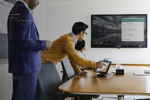 Office workers starting Google Meet from touch controller