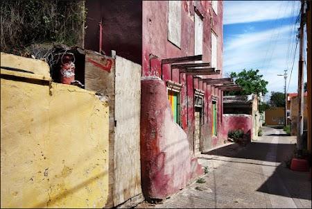 rood geverfd huis met gele muur in het verlengde en schaduwen op straat