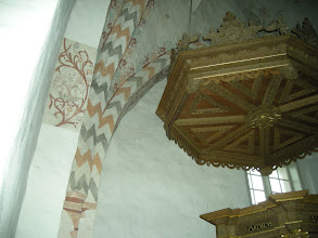 Photo: The pulpit with a self-portrait of the artist on the support beam on the left.