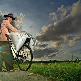 A farmer carrying a sack of fertilizer in Western Java by Krus Haryanto - People Portraits of Men