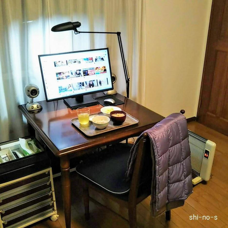 パソコンが置いてあるテーブルで食事