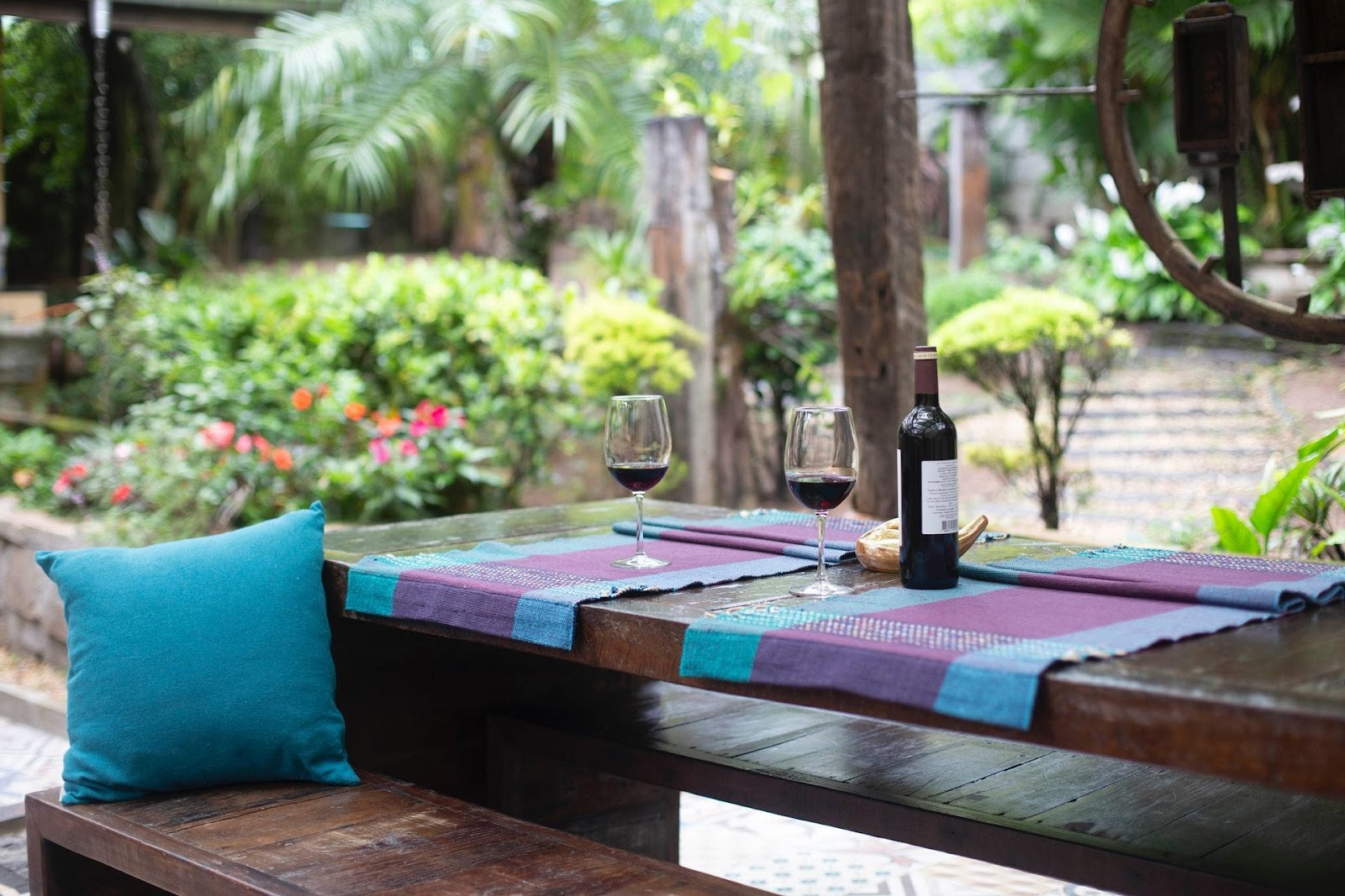A bottle of wine and glasses on a table in an outside sitting area.