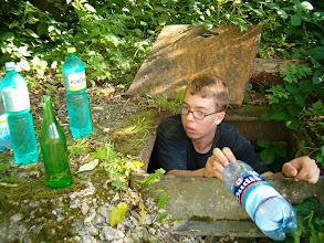 Photo: David plní ve studni láhve vodou
